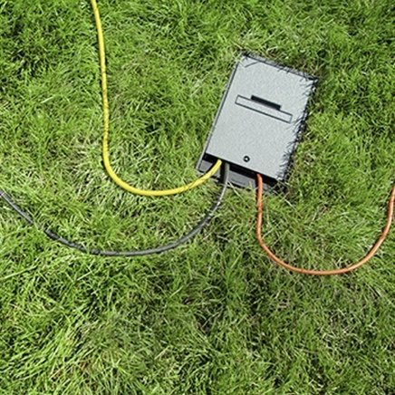 Overhead view of outdoor ground box installed in grass