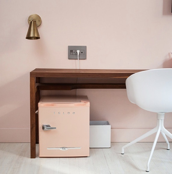 Hotel desk with pink wall and adorne charging center