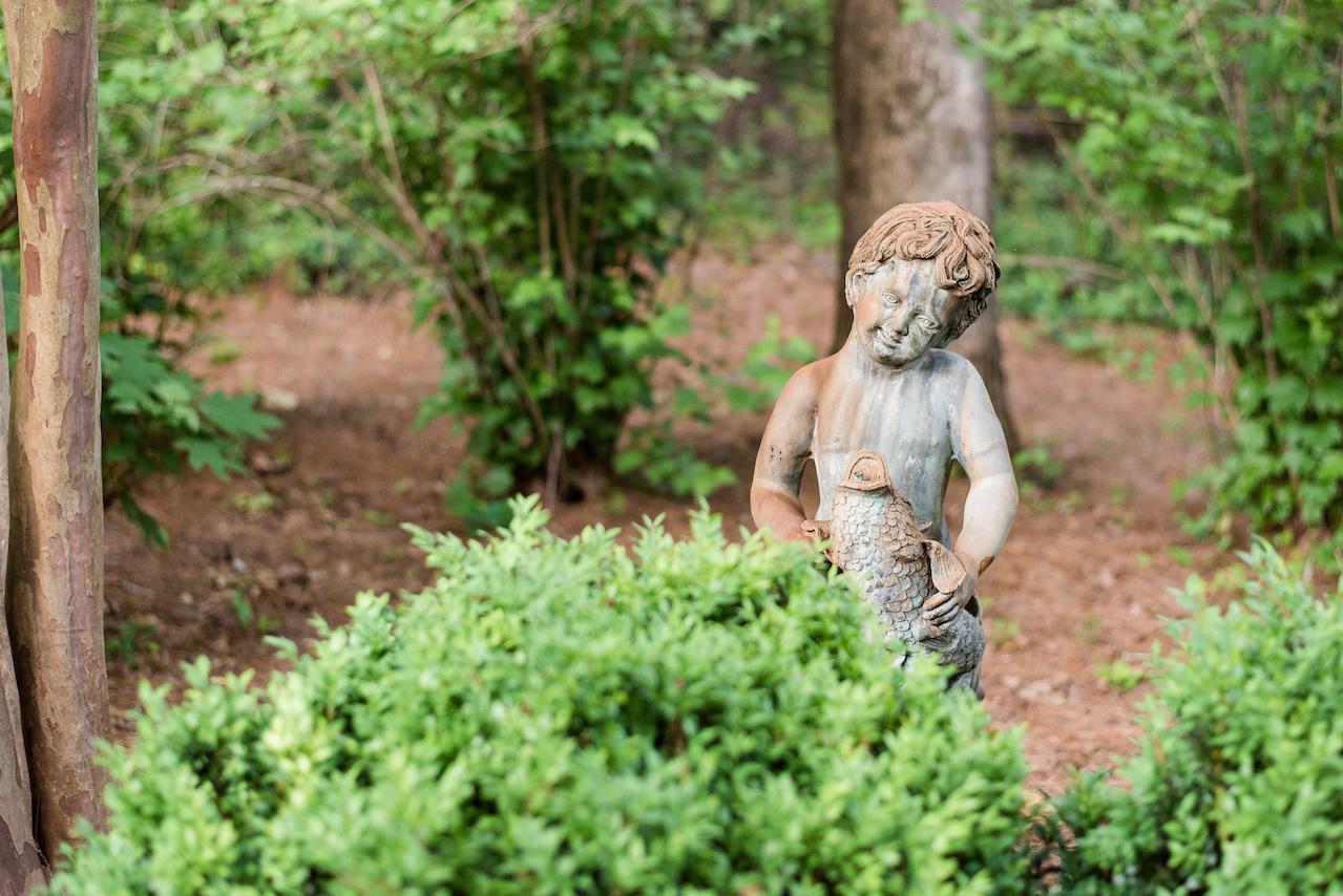 A cherub peeks into the mossy garden.