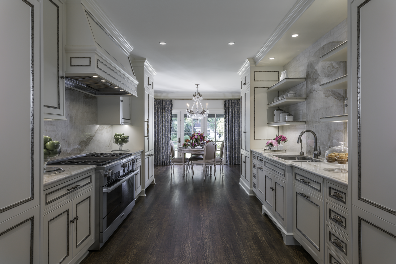 The simple elegance of the white cabinetry and marble counter tops in Ami's kitchen contrasts exquisitely with the dark-brown, hard-wood flooring. At the far end of the kitchen's gallery sits her well-appointed tabletop rife with magnificent elements for entertaining friends for brunch.