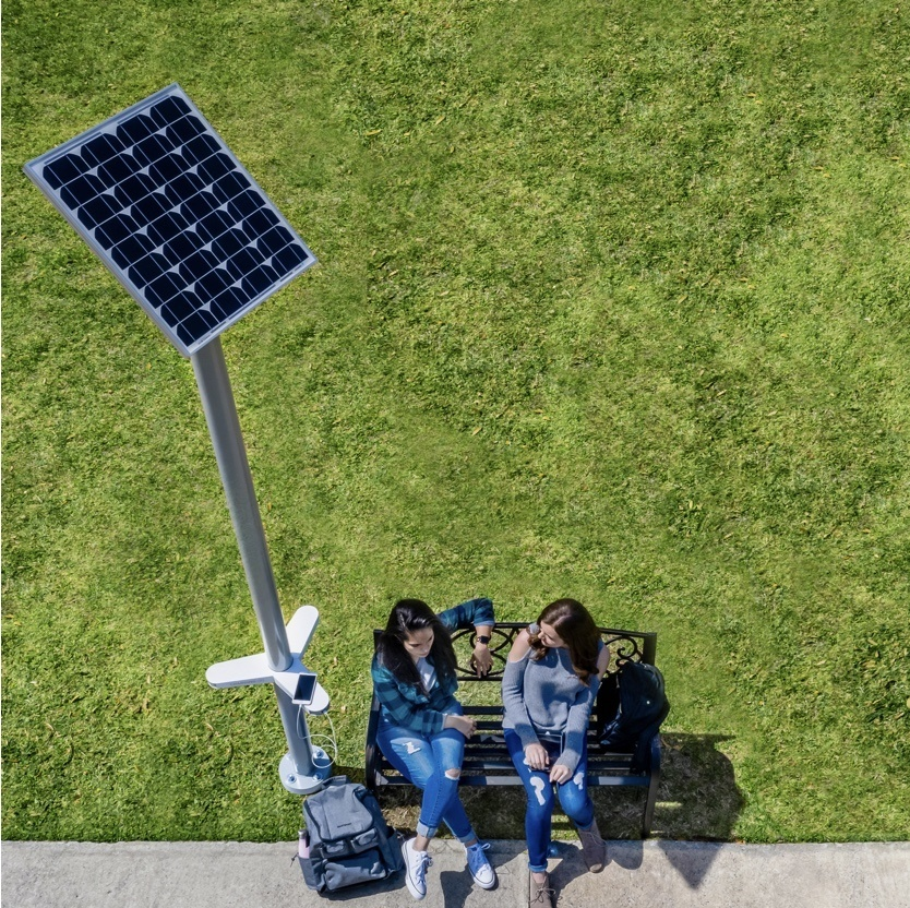Overhead view of two people sitting at bench next to solar charging station