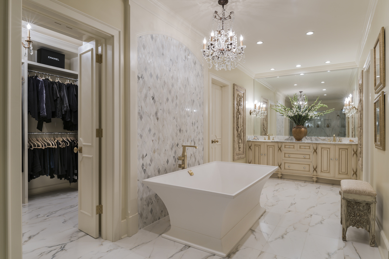 A beautiful Italian chandelier that enhanced and complemented flanking wall sconces, combined with stunning crystal vanity knobs, generates a glamorous atmosphere in this bathroom. Ami used marble and other architectural elements to evoke one single view of the space without separate lines of vision was key, as part of her design plan for the space.