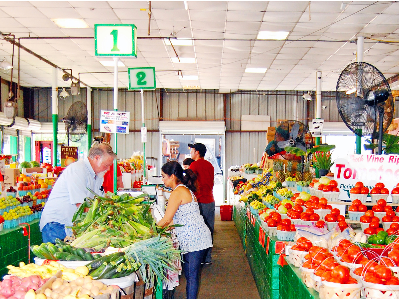 Large fans keep customers cool as they peruse the colorful rows of fresh veggies.