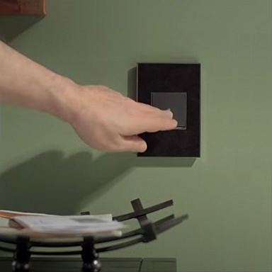 Hand touching adorne dimmer with black wall plate