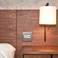 White outlet with silver wall plate against wooden headboard