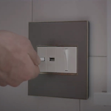 hand plugging into USB outlet next to light switch