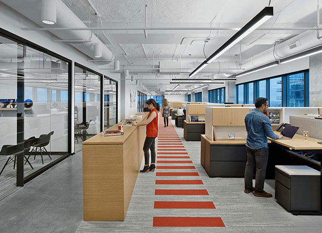 Open office with people standing at desks