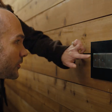 Man watching woman turn on magnesium light switch against wooden wall