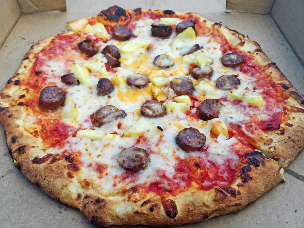 The Southern Hawaii is a perfect mix of Conecuh sausage, fresh cut pineapple and a mix of provolone and mozzarella — Yum!