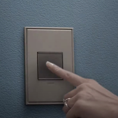 Finger tapping on magnesium light switch on blue wall