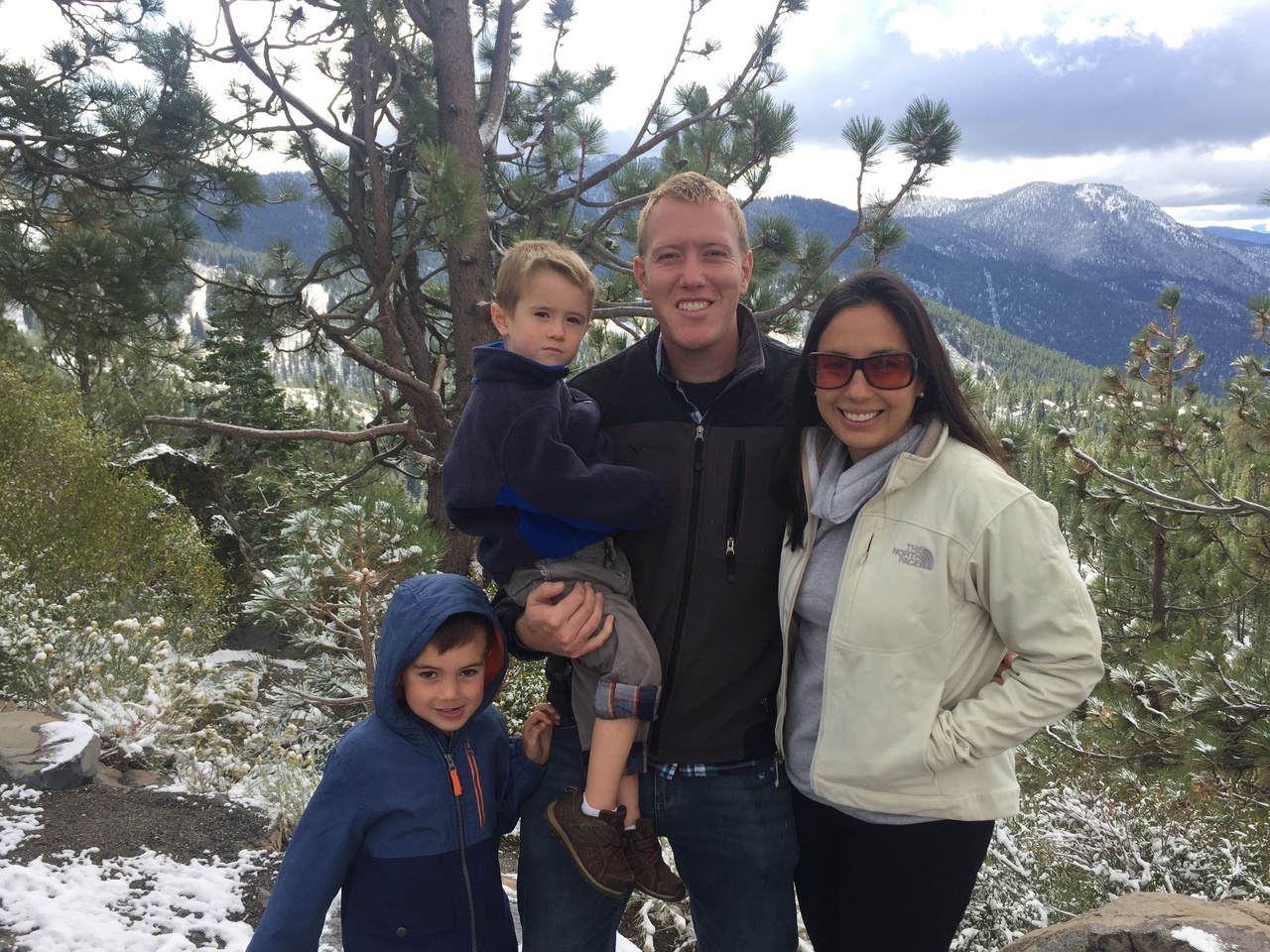 Family photo of Glenn Chamberlain with wife Mari and two young sons with snowy Lake Tahoe region in the background