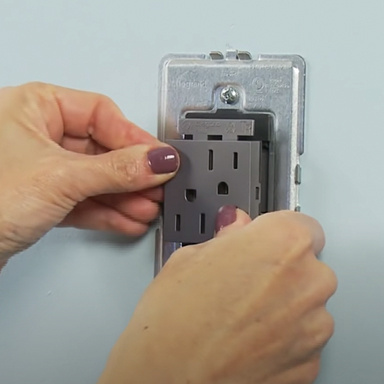 hands installing adorne Collection standary 15 amp outlet in magnesium