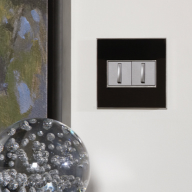 black wall plate with magnesium switches next to art decor