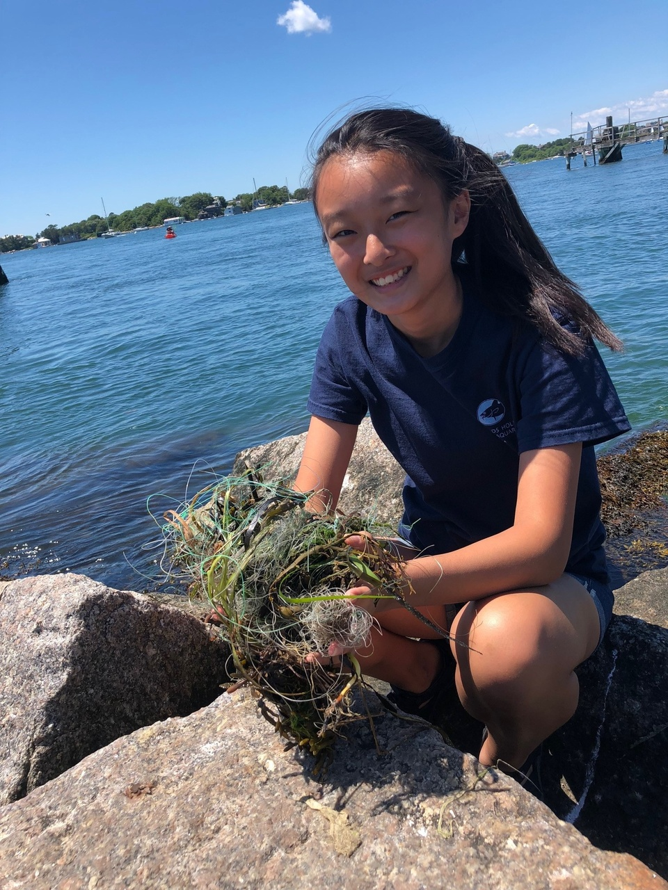 Female intern holding grass and fishing line on the rocks near the water's edge