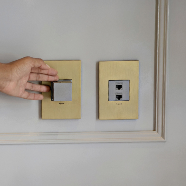adorne Collection pop out and connectivity outlets in magnesium with satin bradd wall plate
