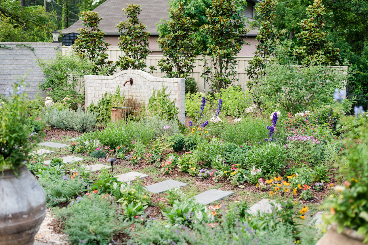 The landscape in the back of the home is more colorful and wild with walkways among the flowers and herbs.