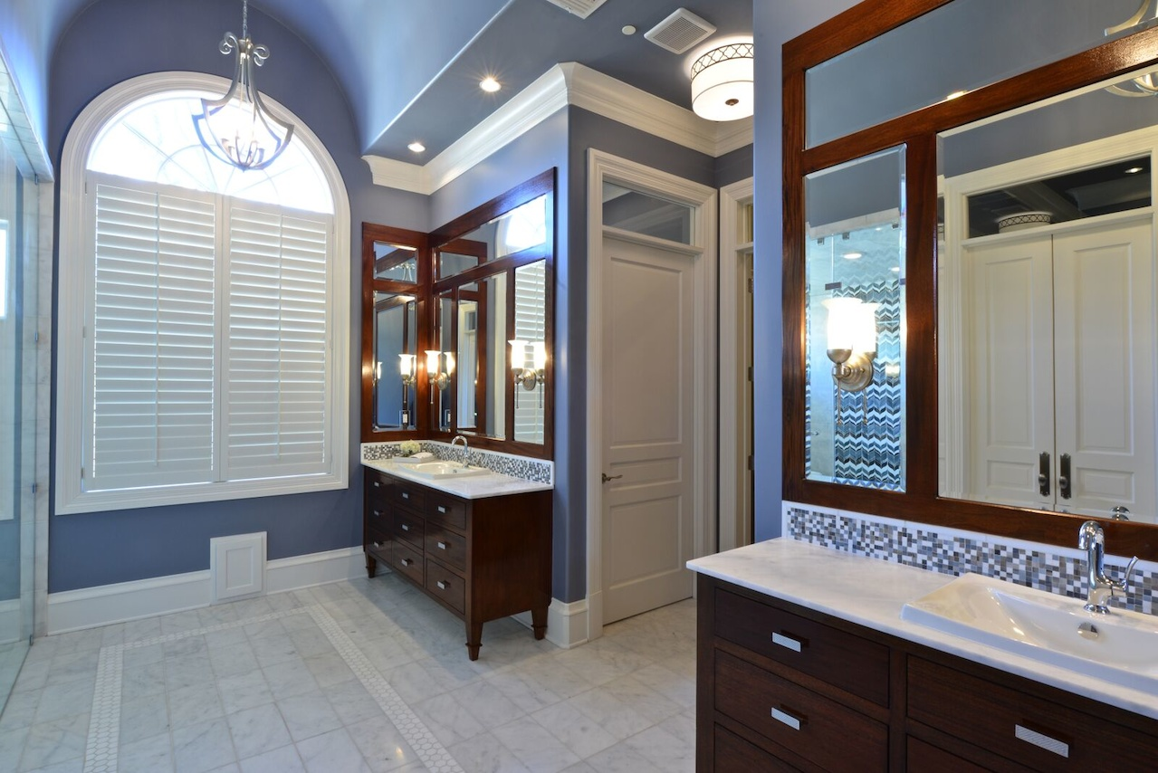 A dark wood stain on the vanities contributes to the rich look, with a mosaic tile backsplash as an added detail.