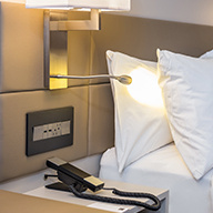 Phone on bedside table with outlets and lamp in hotel room
