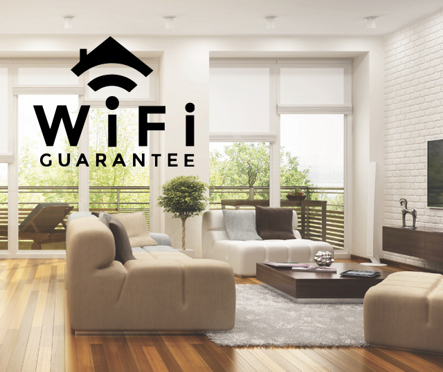 modern living room with large windows and beige sofas with Luxul WiFi assuarance logo