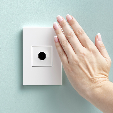 Hand waving over white switch on light blue wall