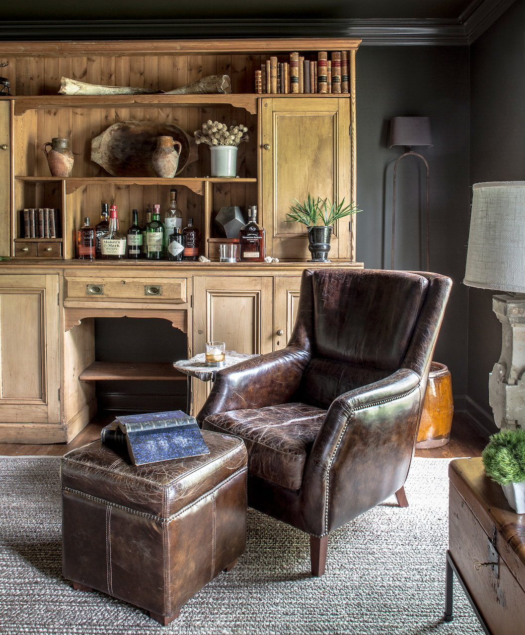 The dark walls and earthy hues enhance the timeless atmosphere of this library / sitting room.