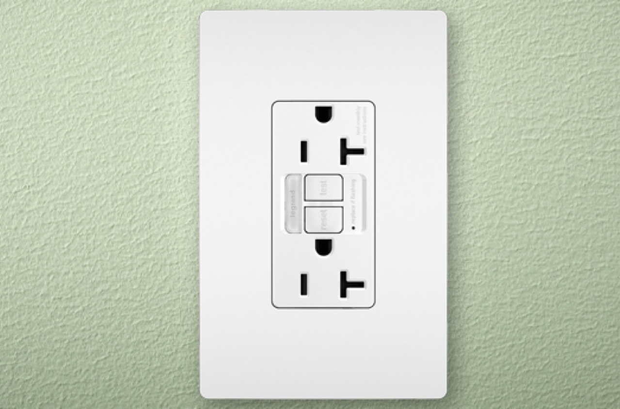 radiant Collection GFCI outlet and screwless wall plate in white on green background