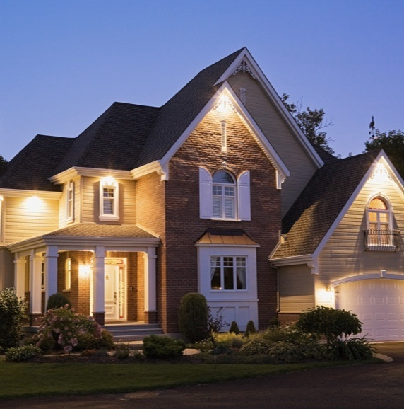 exterior of brick home at night with outdoor lights on