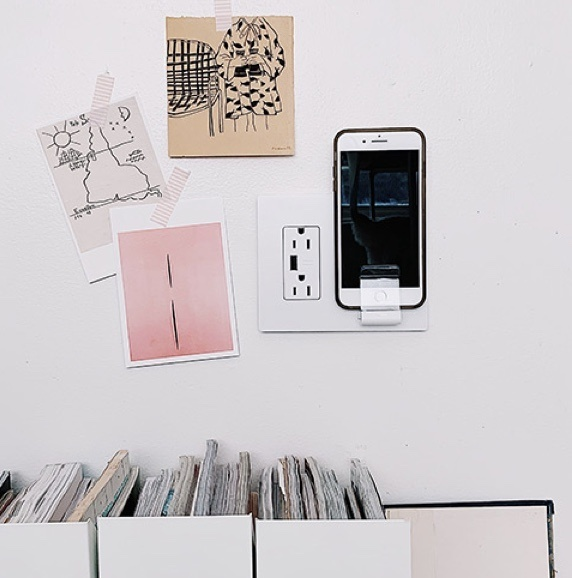 Phone charging in Wireless Charger against white wall in office