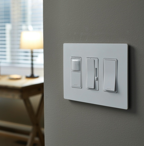 white radiant smart switch and dimmer in living room next to google home