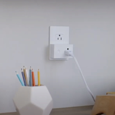 White outlet with smart plug-in switch by desk