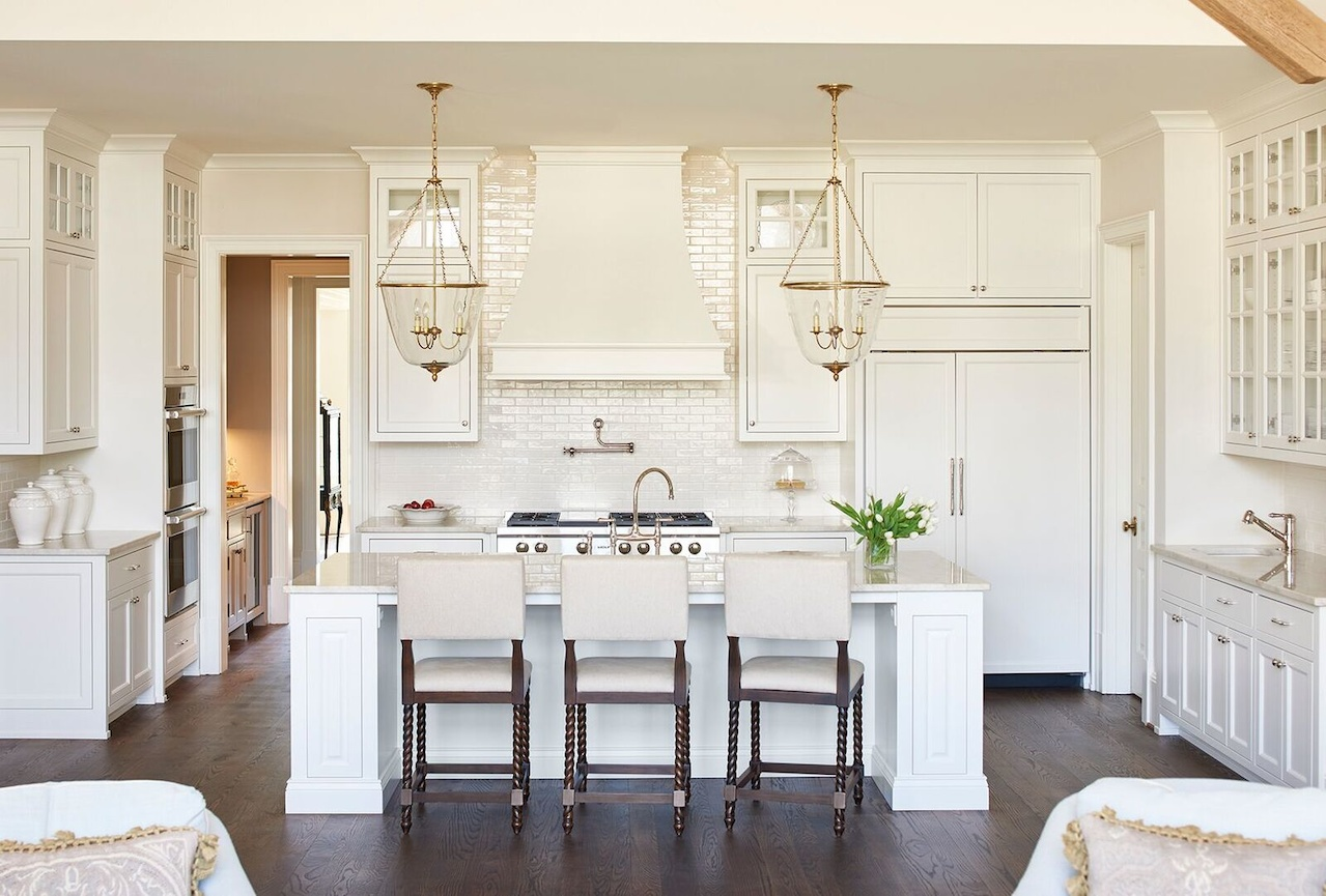 The classic white kitchen features Walker Zanger tiles as backsplash, Visual Comfort lighting and barstools by Ballard Designs.