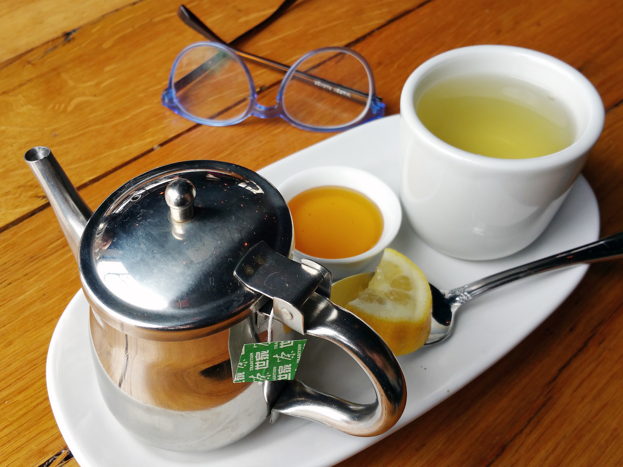 Green tea with honey and lemon at wooden goat
