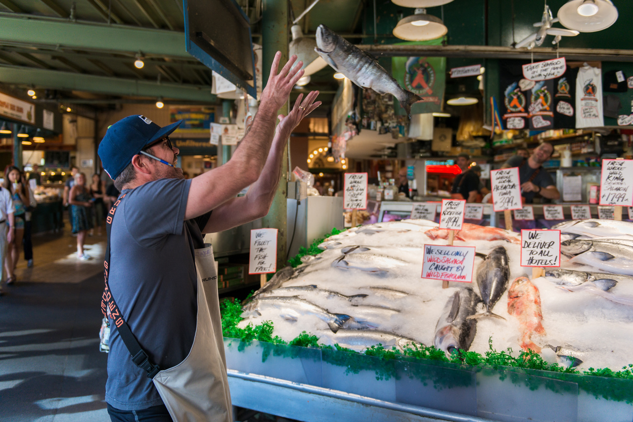 A fish Monger at Pike Place Market catching a fish for tourists late in the day.