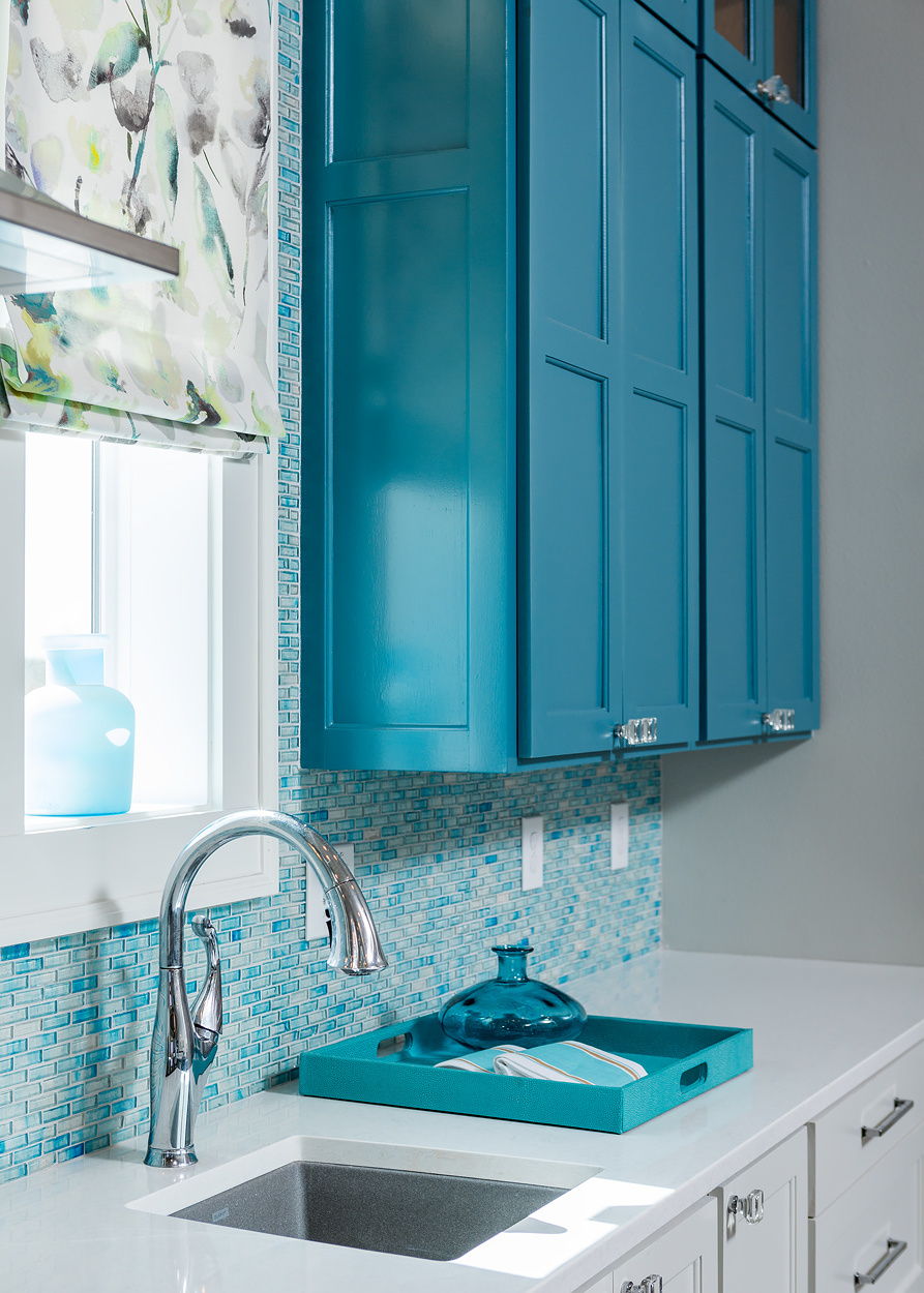 Who says everything needs to match? A single teal cabinet livens up the kitchen corner. Glass knobs go well with the backsplash made of glass tiles.