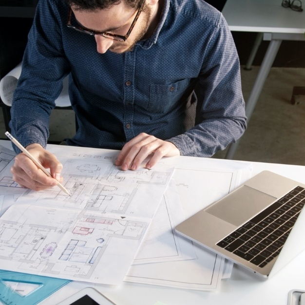 Architect reviewing blue prints next to his laptop