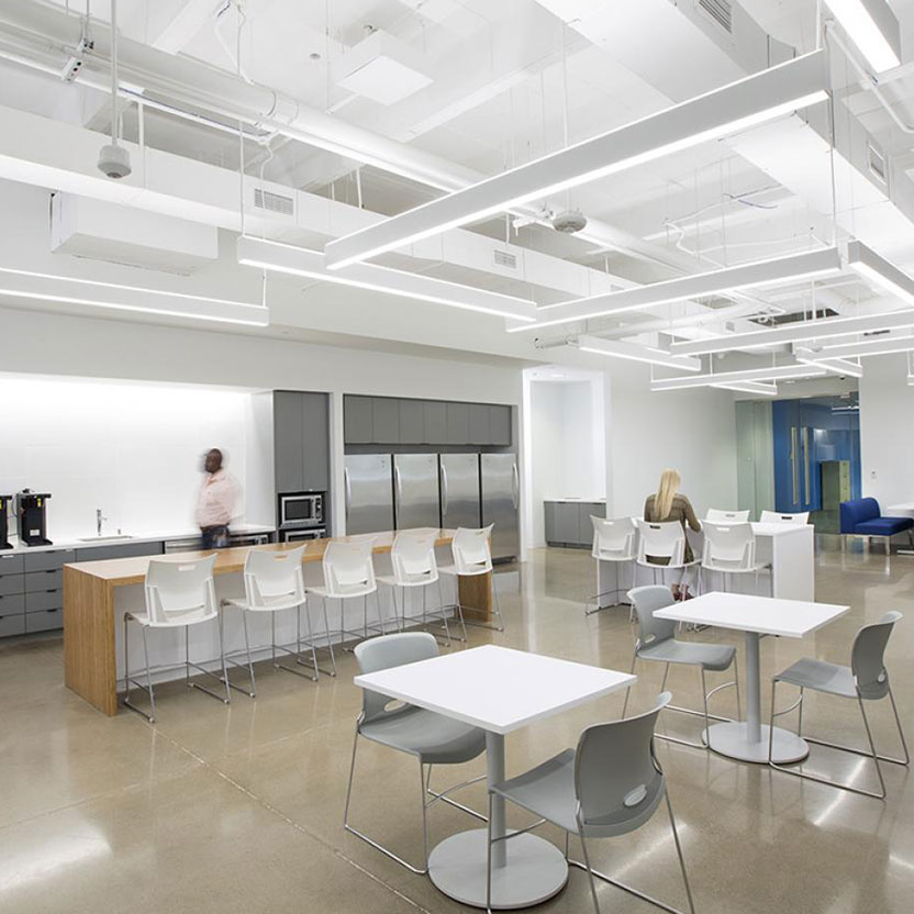 Commercial breakroom area with large round overhead lights