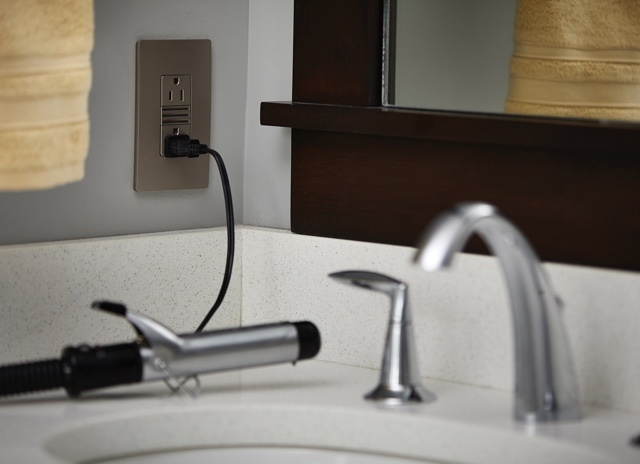 radiant Collection by Legrand nickel GFCI outlet and wall plate on bathroom wall with curling iron plugged in