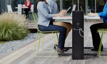 people sitting outdoors charging laptops and cell phones in outdoor power pedestal