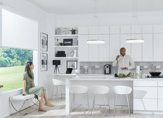 Woman sitting on a bench and man standing by the counter in kitchen area