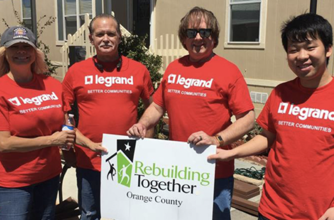 Legrand employees in red shirts in front of a Rebuilding Together sign
