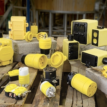 Yellow industrial devices displayed on wooden and concrete platforms