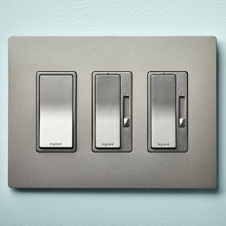 One regular light switch and 2 light switch dimmer combinations, all silver, housed within the same wall plate on a light blue wall