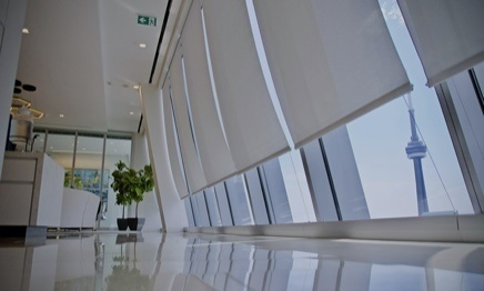 Modern commercial building interior with roller shades on large windows