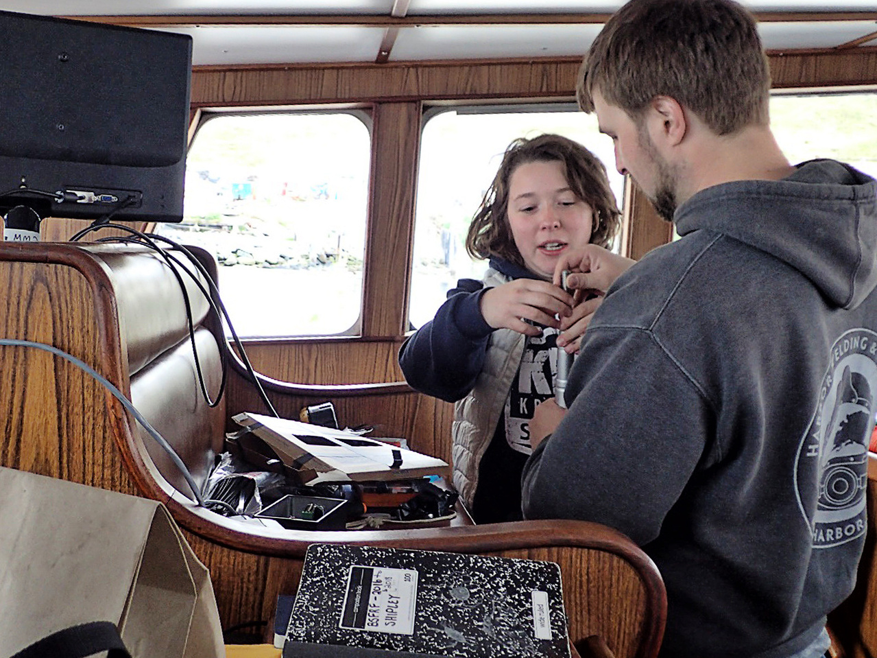 Bering Sea Fisheries Research Foundation biologists Madison Shipley and Charlie Heller prepare sensors for the Tanner crab trawl survey.