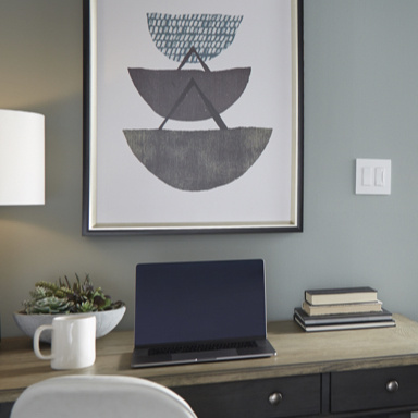 desk with laptop books and plant with wall art