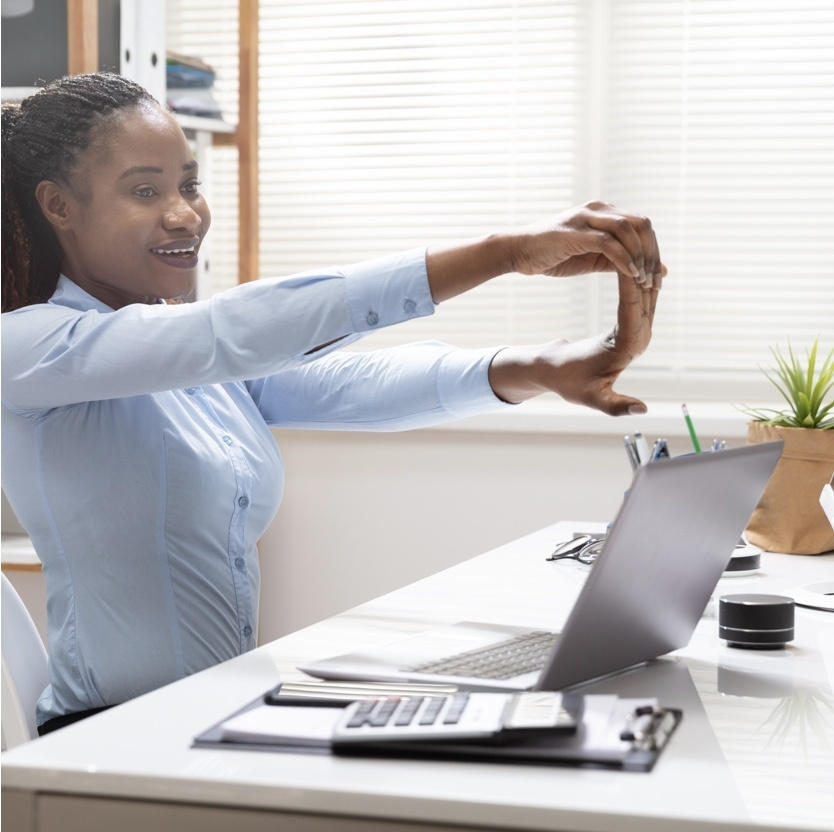 person stretching wrist in front of laptop