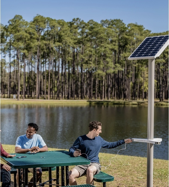 Mobile image of a man sitting at a picnic table using a Solar Charging Kit to charge his device