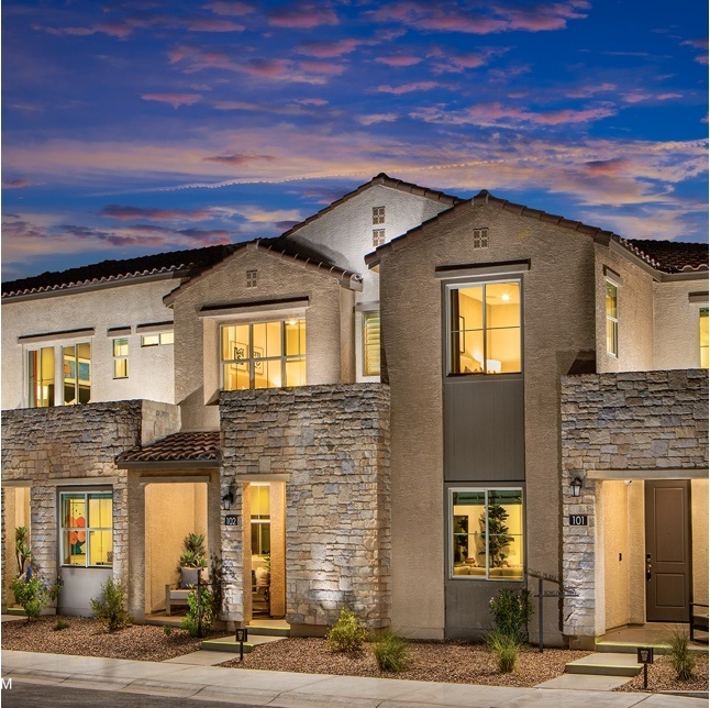 exterior of beige multi-dwelling complex with stone accents at night