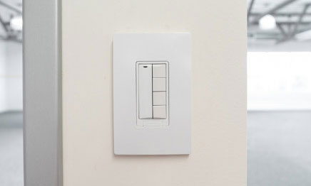 White 5-button switch mounted on an off-white beam in the middle of an empty open office
