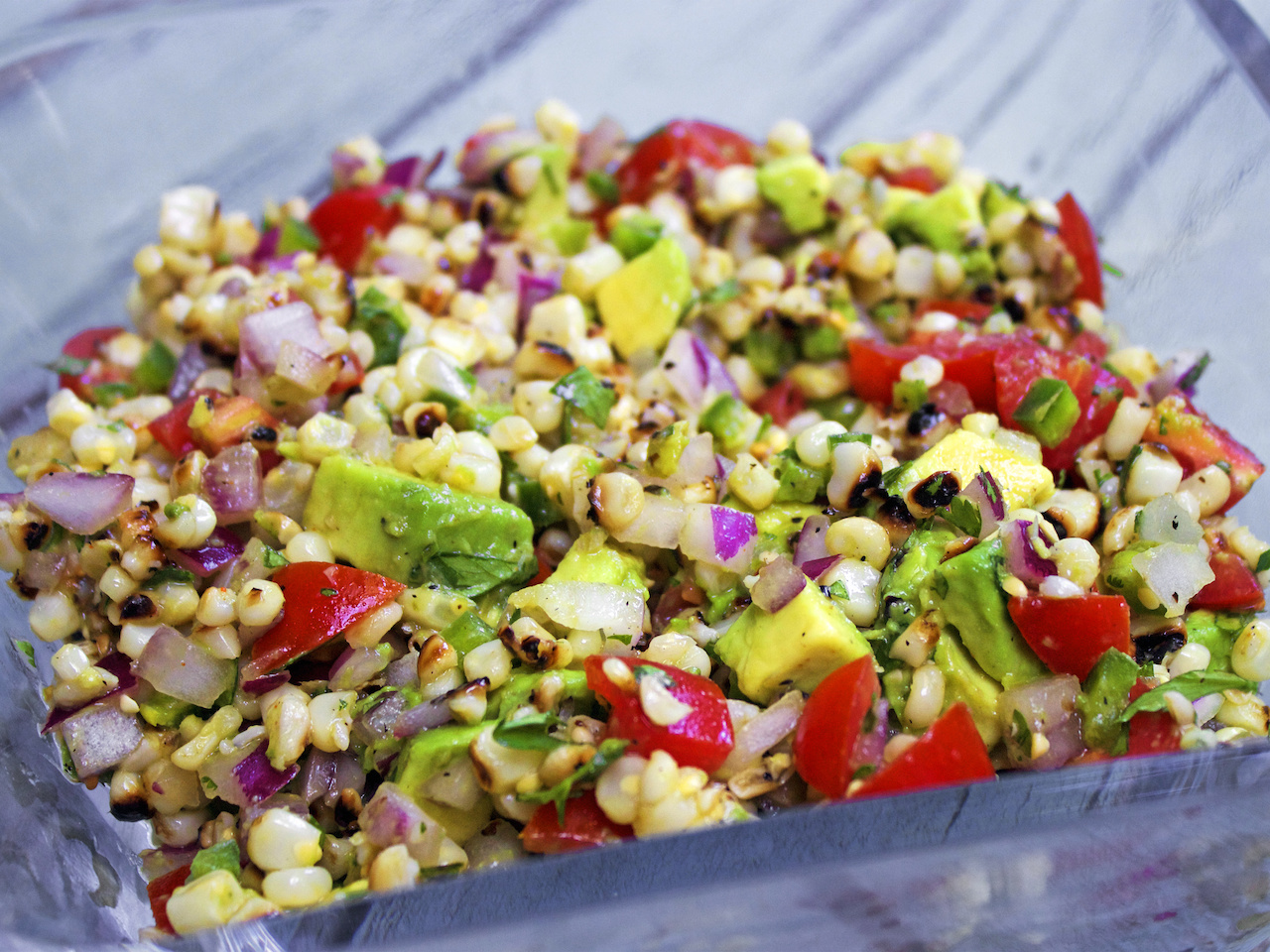 Tomato, corn, avocado and onion salad, done on the grill for maximum taste.